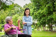 De Aziatische hogere vrouw in boze rolstoel, richt haar vinger, waarschuwend weinig kindmeisje in openluchtpark, grootmoederemoti stock foto