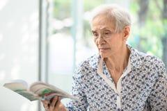 De Aziatische hogere vrouw die een thuis ontspannen boek lezen, bejaarde besteedt hun boek van de vrije tijdlezing royalty-vrije stock foto