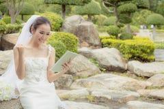 De Aziatische holding van de bruidvrouw en toont digitale tablet zo voelend geluk en blij Stock Afbeelding