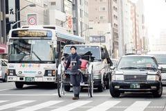 De Aziatische jonge mens trekt een richshaw, voertuigen mens-aangedreven kar met twee wielen in Tokyo, Japan royalty-vrije stock fotografie