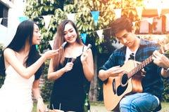 De Aziatische jonge vrouwen die aan vriend met kerel het spelen gitaar voeden zingen stock foto's
