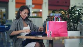 De Aziatische jonge vrouwen met het winkelen doet het bekijken nieuwe kleren sittinf in koffie in zakken stock video