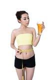 De Aziatische jonge vrouwen slanke pasvorm is drinkt jus d'orange en het meten stock fotografie