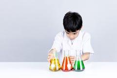 De Aziatische jongen bekijkt de combinatie van de testkleur op wetenschap experimen Stock Fotografie