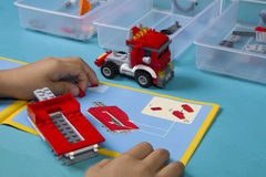 De Aziatische jongen bouwt lego met instructiehandboek Stock Foto's