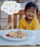 De Aziatische jongen denkt over wiskundig tijdens ontbijt eet stock afbeeldingen