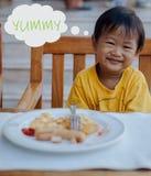 De Aziatische jongen geniet van zijn ontbijt stock afbeelding