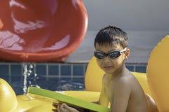 De Aziatische jongen is het gelukkige spelen in de pool royalty-vrije stock afbeeldingen