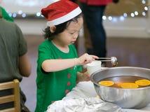 De Aziatische jongen in de kleding van het santakostuum giet jus d'orange in kop stock foto