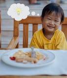 De Aziatische jongen krijgt een idee tijdens eet ontbijt stock afbeelding