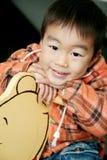 De Aziatische jongen legt op hobbelpaard Stock Foto