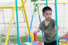 De Aziatische jongen speelt een speelplaats op vaag boom backgroud dorp van grappig Stock Fotografie