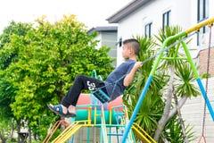 De Aziatische jongen speelt een speelplaats op vaag boom backgroud dorp van grappig Stock Afbeeldingen