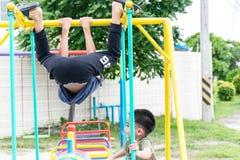 De Aziatische jongen speelt een speelplaats op vaag boom backgroud dorp van grappig Stock Foto's