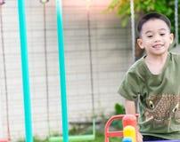 De Aziatische jongen speelt een speelplaats op vaag boom backgroud dorp van grappig Stock Foto