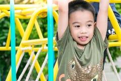De Aziatische jongen speelt een speelplaats op vaag boom backgroud dorp van grappig Royalty-vrije Stock Afbeelding