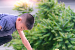 De Aziatische jongen speelt een speelplaats op vaag boom backgroud dorp van grappig Royalty-vrije Stock Foto's