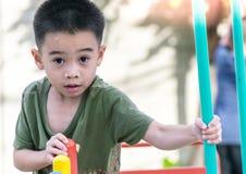 De Aziatische jongen speelt een speelplaats op vaag boom backgroud dorp van grappig Royalty-vrije Stock Fotografie