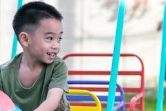 De Aziatische jongen speelt een speelplaats op vaag boom backgroud dorp van grappig Royalty-vrije Stock Foto