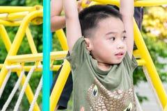 De Aziatische jongen speelt een speelplaats op vaag boom backgroud dorp van grappig Royalty-vrije Stock Afbeeldingen