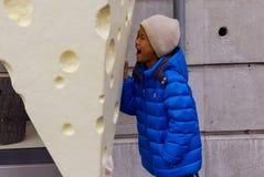 De Aziatische jongen wil een grote kaas stock foto