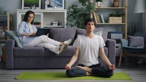 De Aziatische kerel concentreerde zich op meditatie terwijl vrouw het werken thuis met computer stock videobeelden