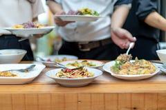 De Aziatische kerel dicht tot de handen holt het traditionele Thaise voedsel uit; Somtum, omelet, Thaise soep, enz. , op de houte royalty-vrije stock fotografie