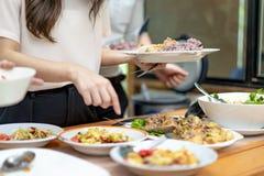 De Aziatische kerel dicht tot de handen holt het traditionele Thaise voedsel uit; Somtum, omelet, Thaise soep, enz. , op de houte stock foto's