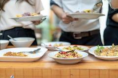 De Aziatische kerel dicht tot de handen holt het traditionele Thaise voedsel uit; Somtum, omelet, Thaise soep, enz. , op de houte royalty-vrije stock afbeeldingen