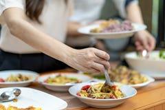 De Aziatische kerel dicht tot de handen holt het traditionele Thaise voedsel uit; Somtum, omelet, Thaise soep, enz. , op de houte royalty-vrije stock afbeelding
