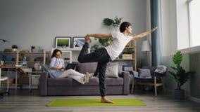 De Aziatische kerel die yoga doen oefent wanneer vrouw het spreken op mobiele telefoon gebruikend laptop uit stock videobeelden