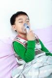 De Aziatische kind sluitende ogen en houdt een inhaleertoestel van de maskerdamp voor trea royalty-vrije stock foto
