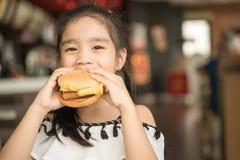 De Aziatische Kinderen eten het Hof van het de Hamburgervoedsel van de kippenkaas stock foto