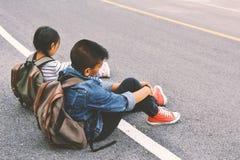 De Aziatische kinderen worden vermoeid na het backpacking op aardachtergrond Royalty-vrije Stock Foto's