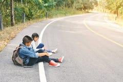 De Aziatische kinderen worden vermoeid na het backpacking op aardachtergrond Royalty-vrije Stock Foto
