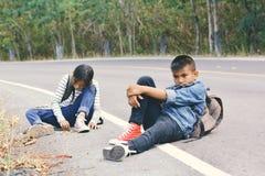 De Aziatische kinderen worden vermoeid na het backpacking op aardachtergrond Royalty-vrije Stock Afbeelding