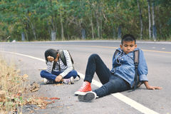 De Aziatische kinderen worden vermoeid na het backpacking op aardachtergrond Stock Afbeelding