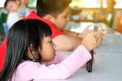 De Aziatische de kindjongen en meisjes zijn verslavende het spelen tablet en mobiele telefoons stock foto's