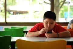 De Aziatische kindjongen is verslavende het spelen mobiele telefoons royalty-vrije stock afbeeldingen