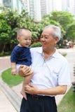 De Aziatische kleinzoon van de grootvaderholding royalty-vrije stock afbeeldingen