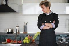 De Aziatische kok in de keuken bereidt voedsel in een kokkostuum voor stock afbeelding