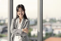De Aziatische langharige onderneemster kijkt goed in kostuum het glimlachen Sta royalty-vrije stock foto