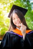 De Aziatische leuke graduatie van het vrouwenportret met groene aardachtergrond Stock Foto's