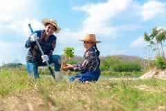 De Aziatische mamma en kind het jonge boompjeboom van meisjesinstallaties in de aardlente voor vermindert globale verwarmende de  stock afbeeldingen