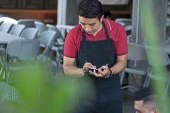 De Aziatische mannelijke kelner met schort schrijft orden van costumieren bij koffie op achtergrond stock foto