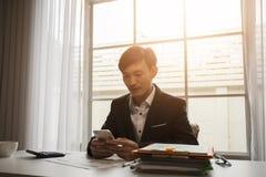 De Aziatische mannelijke zakenman gebruikt een toepassing van de taxitelefoon stock foto's
