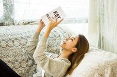 De Aziatische meisjes overhandigen holding boek en het glimlachen gelukkig op de laag in het huis met ontspanning, concept het pl royalty-vrije stock fotografie