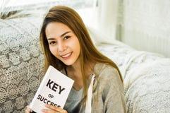 De Aziatische meisjes overhandigen holding boek en het glimlachen gelukkig op de laag in het huis met ontspanning, concept het pl stock fotografie