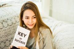 De Aziatische meisjes overhandigen holding boek en het glimlachen gelukkig op de laag in het huis met ontspanning, concept het pl royalty-vrije stock foto
