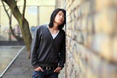 De Aziatische mens die van de herfst omhoog mager op de muur kijkt Stock Afbeelding